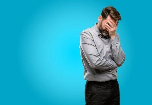 Un homme frustré, la tête à la main. | Source : Shutterstock
