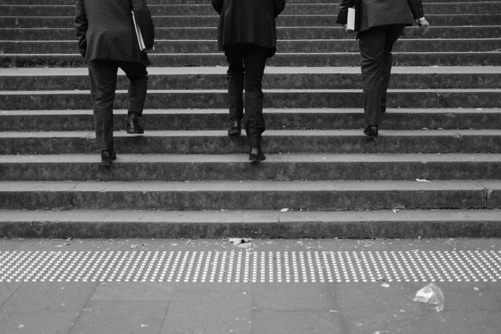 Three men moving up the stairs. | Photo: Getty Images