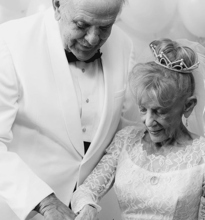 A picture of 79-year-old Karen Ryan and 79-year-old Gary Ryan recreating the moment they cut their cake on their wedding day. | Source: instagram.com/nikkiryanphotography