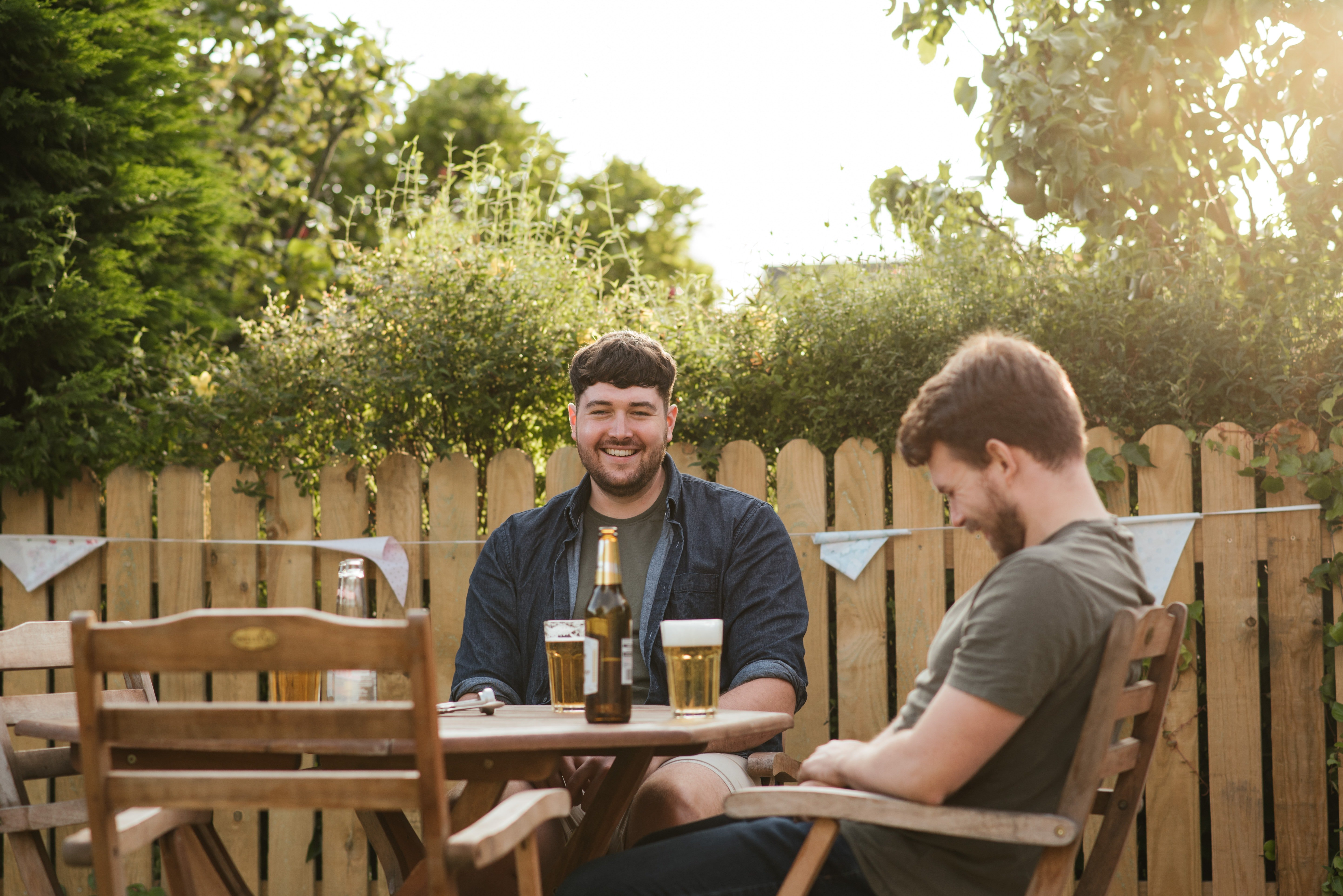Two men drinking beers outside.   Pexels/  Anete Lusina