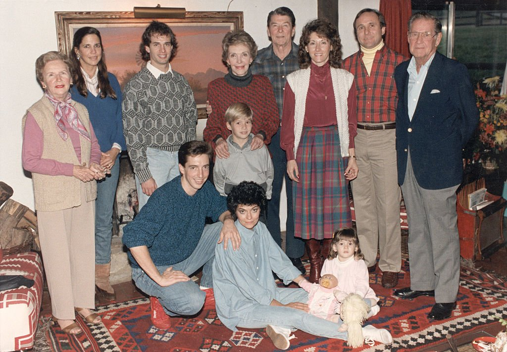 Portrait of President Ronald Reagan and First Lady Nancy Reagan with their family at Rancho del Cielo near Santa Barbara, California, November 28, 1985. Standing (L-R): Bess Reagan, Patti Davis, Paul Grilley, Cameron Reagan, Nancy Reagan, the President, Colleen and Michael Reagan, and Neil Reagan. Foreground, (L-R): Ron, Doria, and Ashley Marie Reagan. | Source: Getty Images