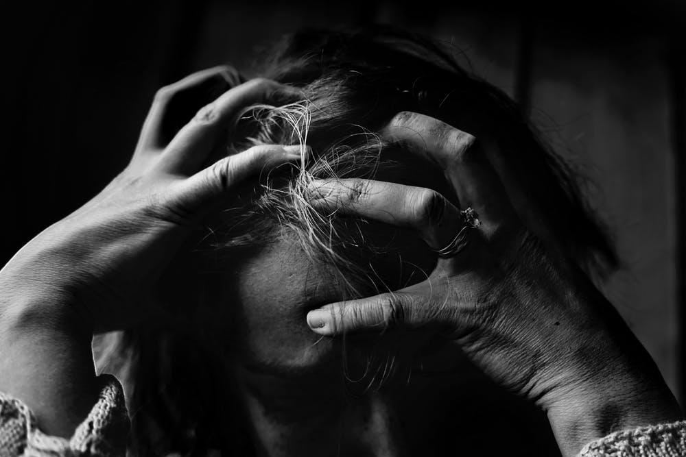Une femme tenant sa tête dans ses mains. l Source: Pexels