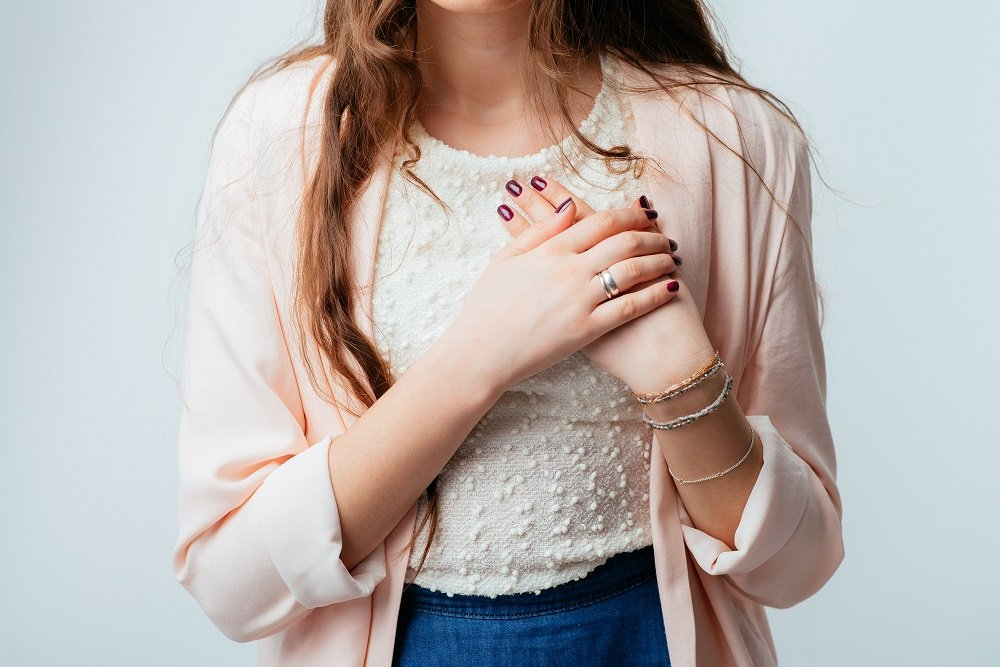 Mujer se toca el pecho. Fuente: Shutterstock