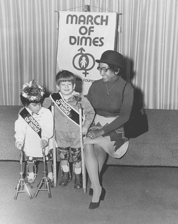 A March of Dimes fund raising event with woman on a stage sitting with two children holding crutches, in 1970 | Source: Getty Images