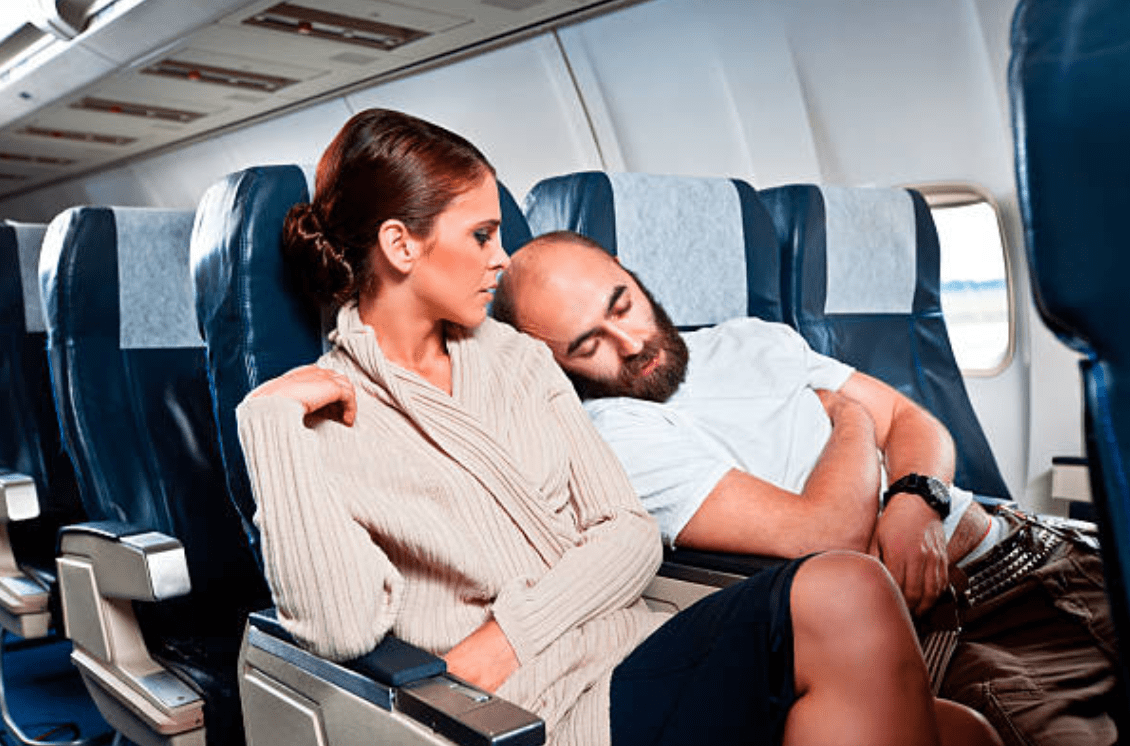 Stranger sleeps on woman's shoulder on a plane | Source: Getty Images