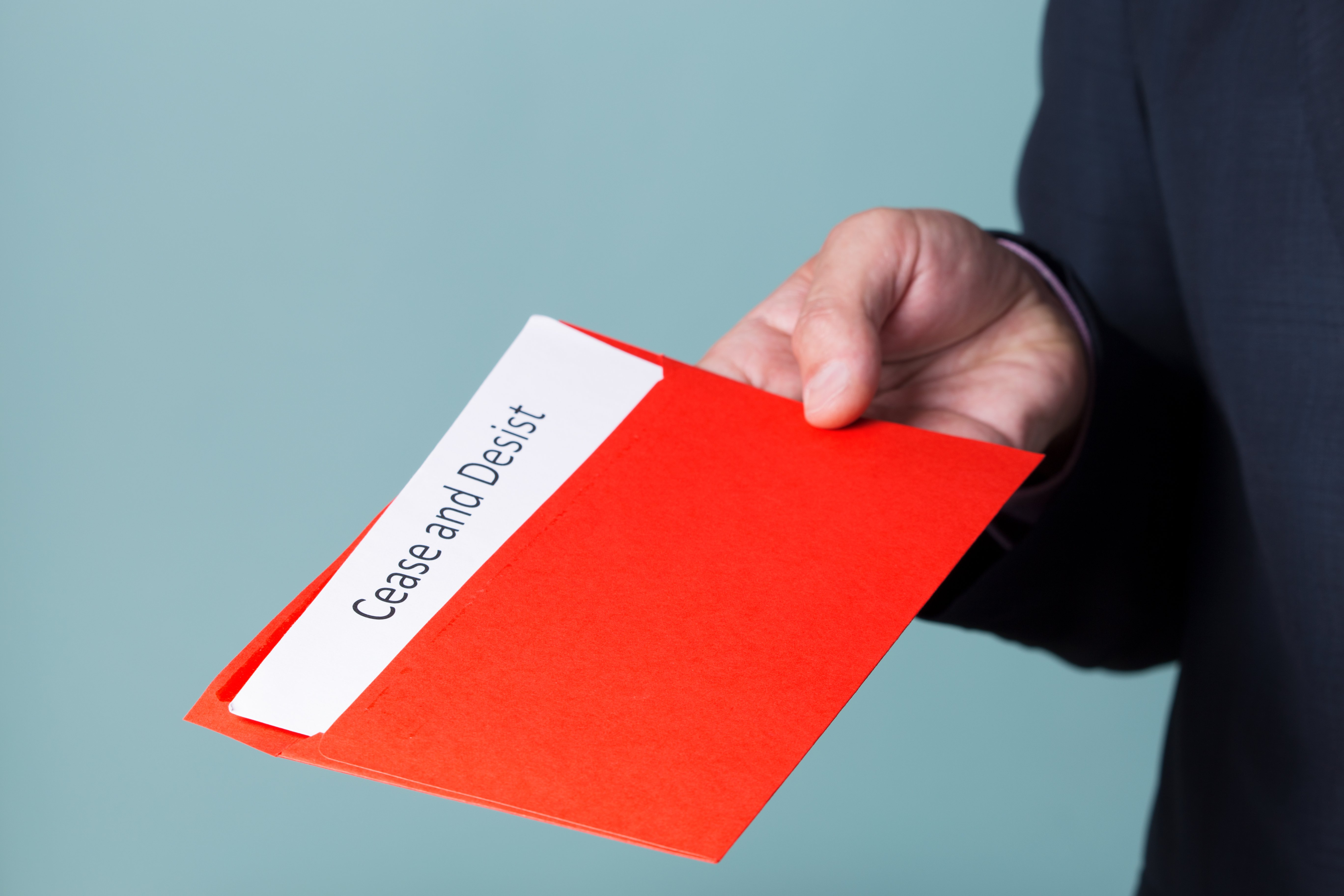 A man holding a cease and desist letter in red folder.   Source: Shutterstock