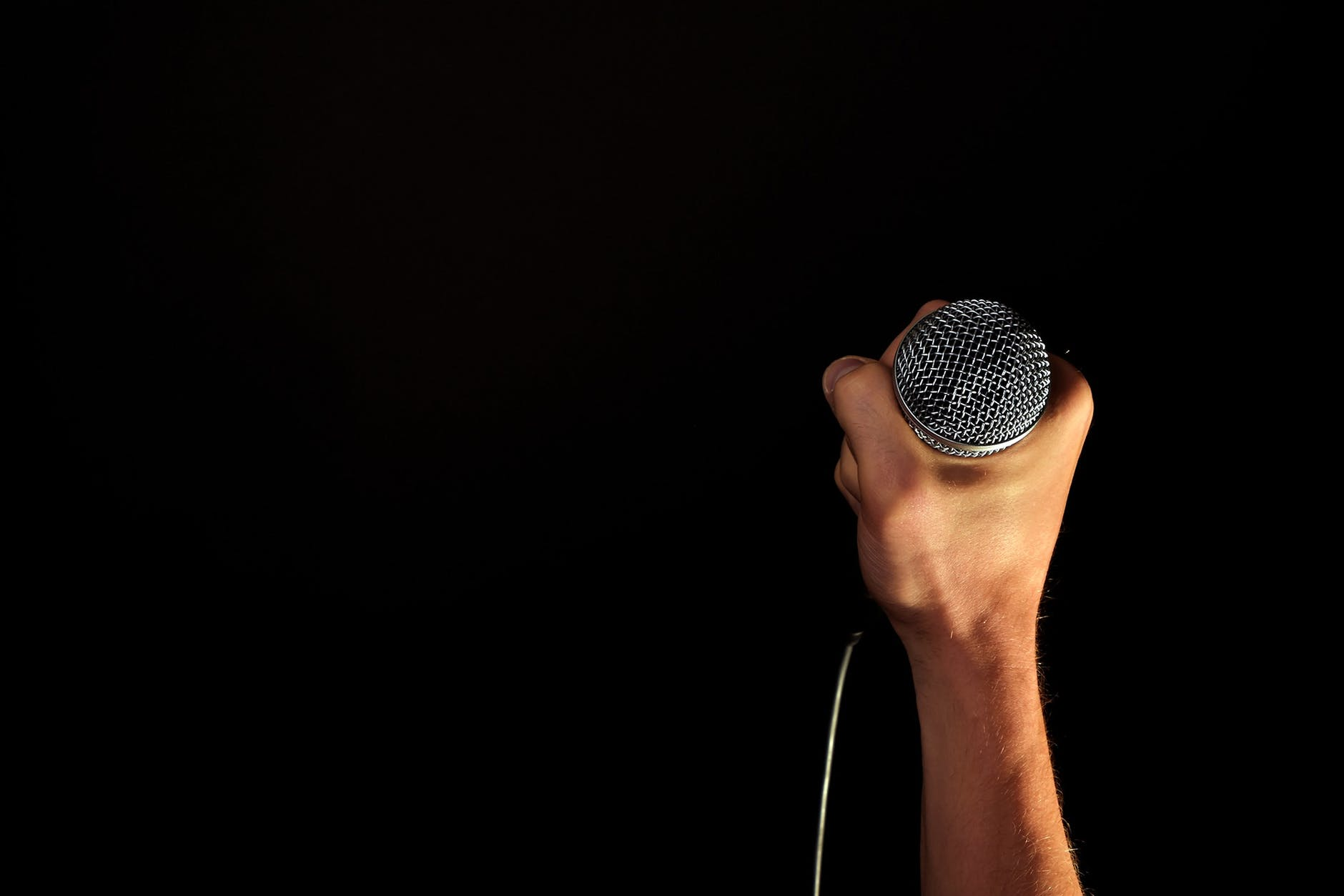 Hand holding a microphone   Source: Pexels