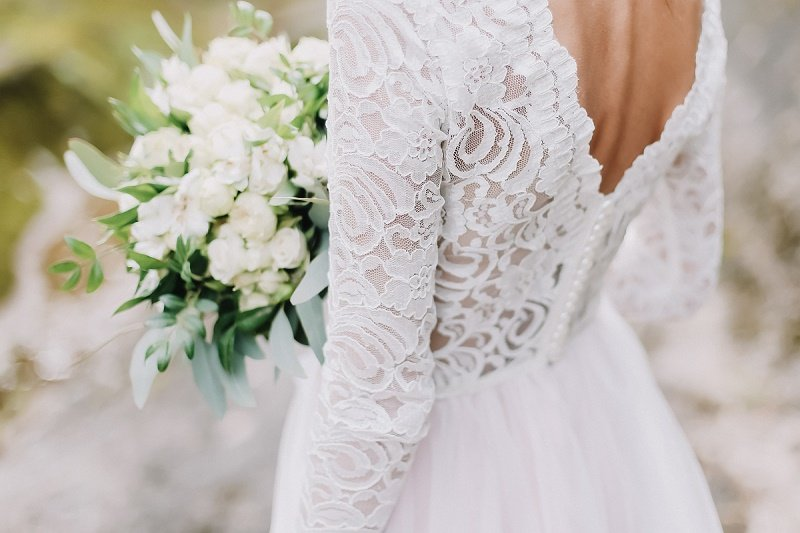 Woman in a wedding dress holding a bouquet of flowers. | Image: Shutterstock.