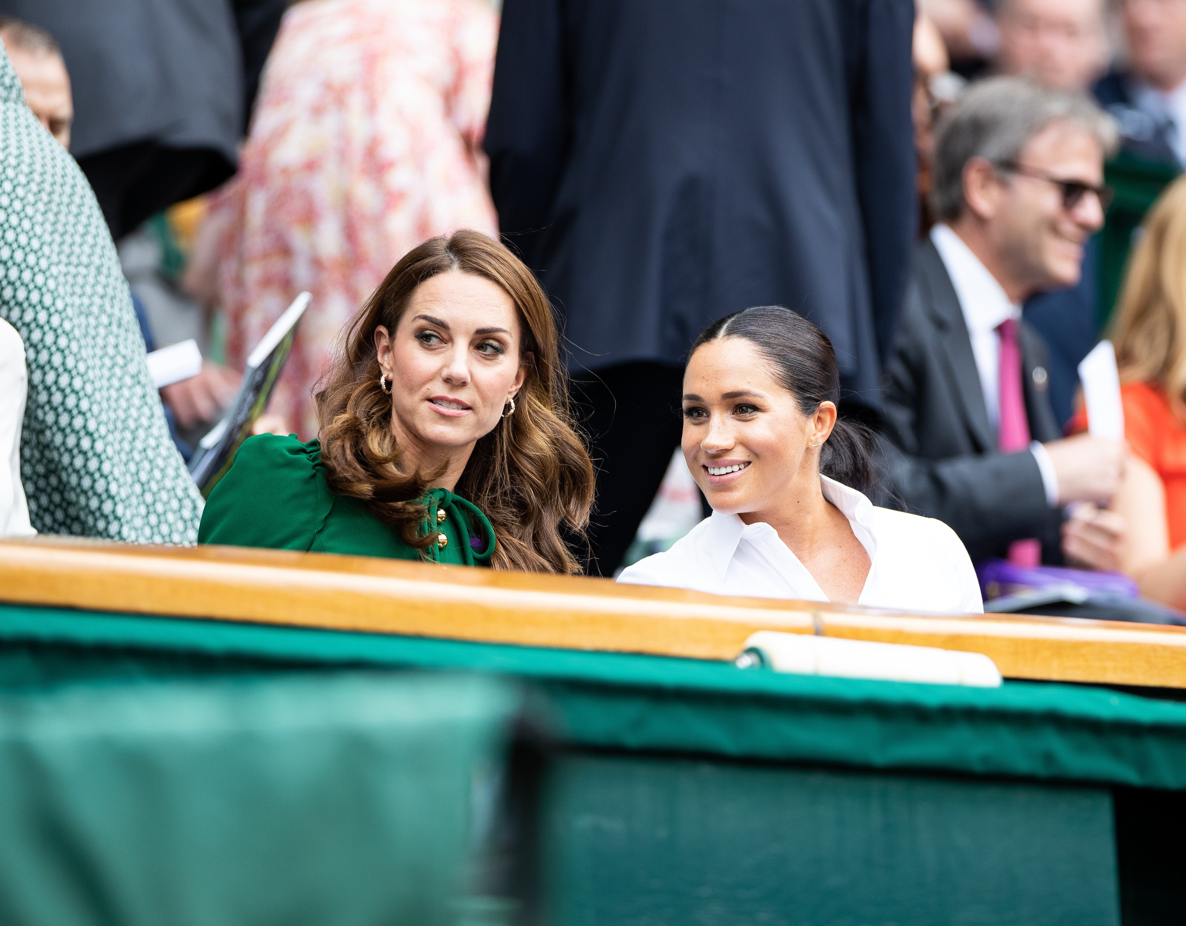 Kate Middleton, Duchess of Cambridge, talks with Meghan Markle, Duchess of Sussex in the royal box before the start of the Women's Singles Final at The Wimbledon Lawn Tennis Championship at the All England Lawn and Tennis Club at Wimbledon on July 13, 2019 in London, England | Photo: Getty Images