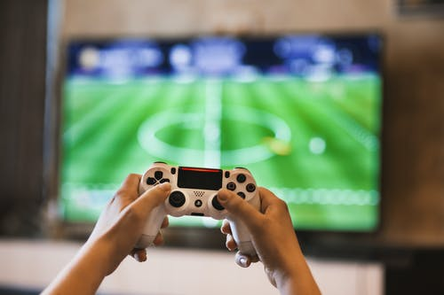 Boy playing with a PlayStation   Source: Pexels