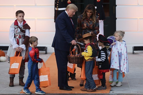 President Donald Trump and first lady Melania Trump hand out candy to trick-or-treaters during a Halloween at the White House event at the South Portico of the White House. | Photo: Getty Images