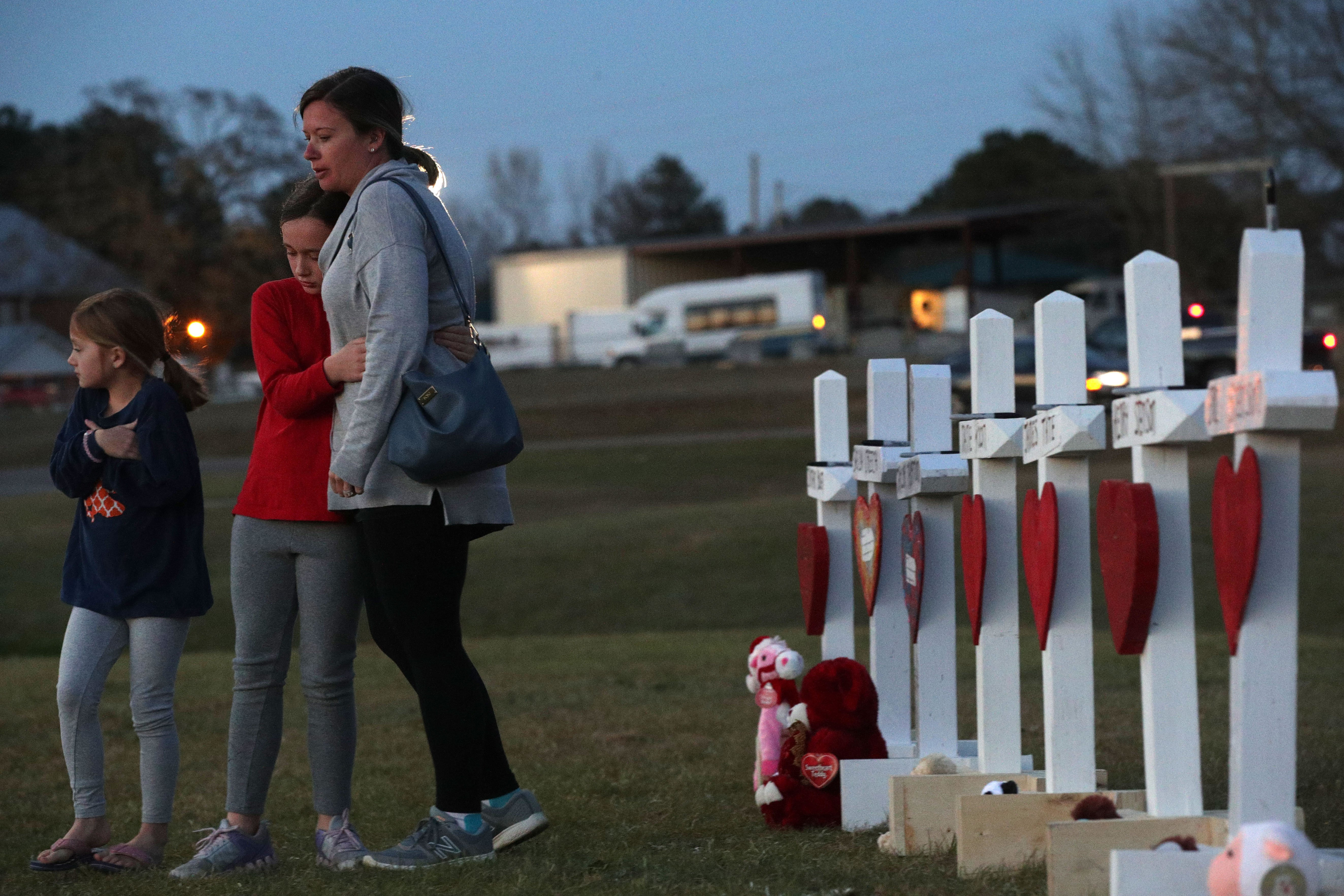 A family paying their respects to a friend who passed during the Tornado in Opelika, Alabama | Photo: Getty Images