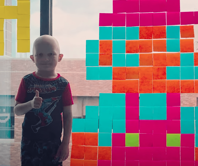 A boy battling cancer smiles as he stands next to his creative Post-it note art | Photo: Youtube/Good Morning America