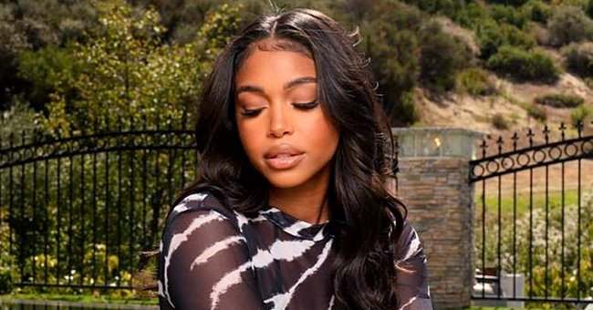 Lori Harvey Hides Her Enviable Body in a Sheer Black Dress by Matte Swim as She Poses by a Pool