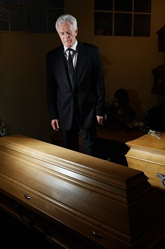 Photo of a man standing in a funeral parlor | Photo: Getty Images