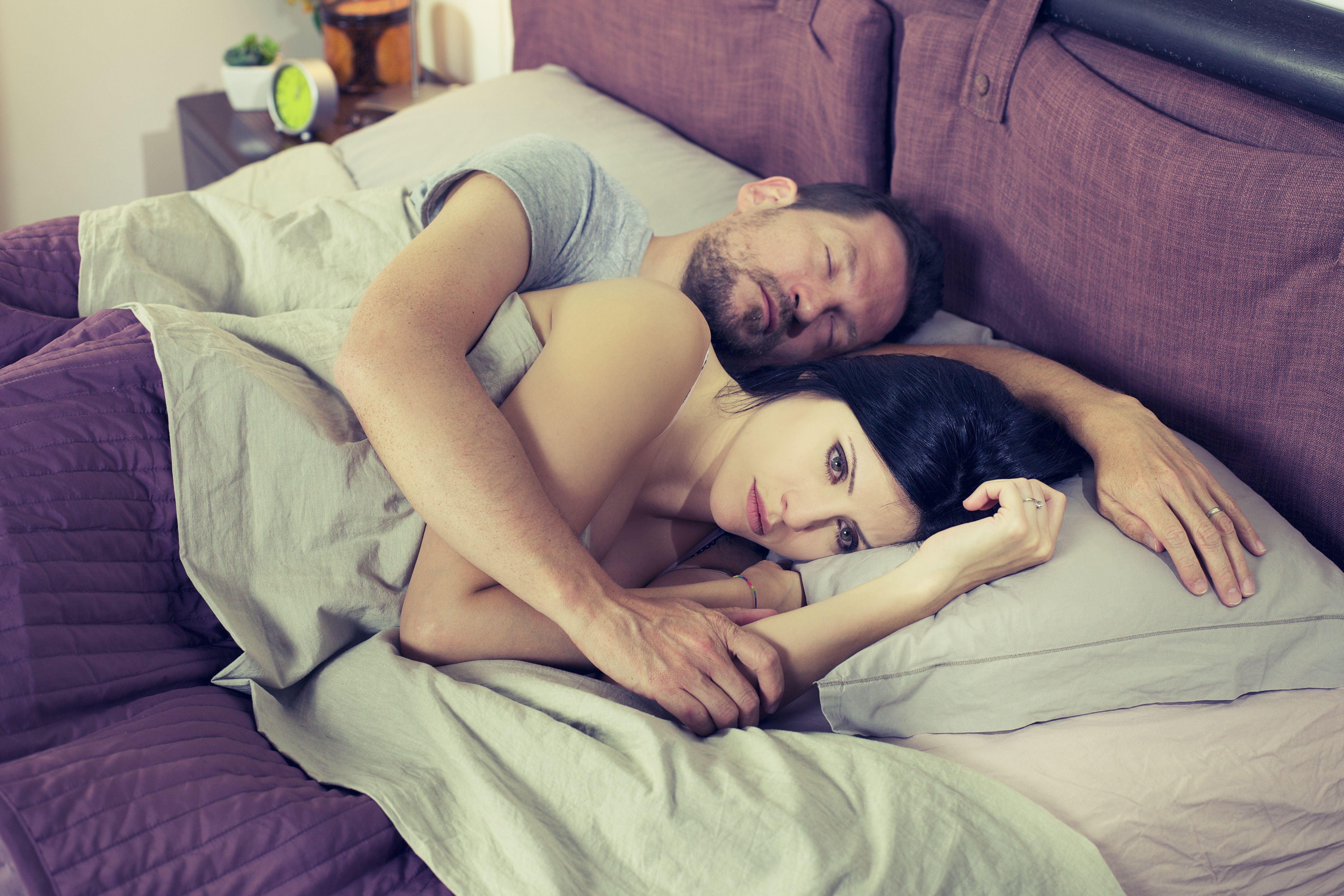 A woman looks worried while her husband sleeps beside her. | Source: Shutterstock