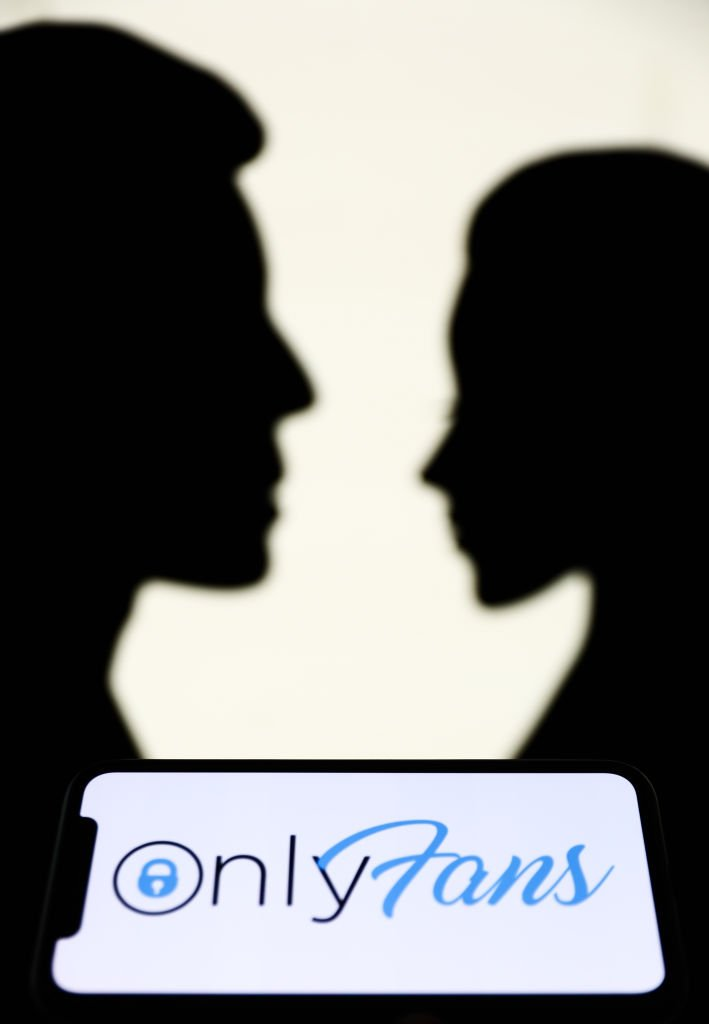 OnlyFans logo displayed on a phone screen is seen with paper silhouettes looking like a man and a woman in the background in this illustration photo taken in Krakow, Poland on August 25, 2021. | Source: Getty Images