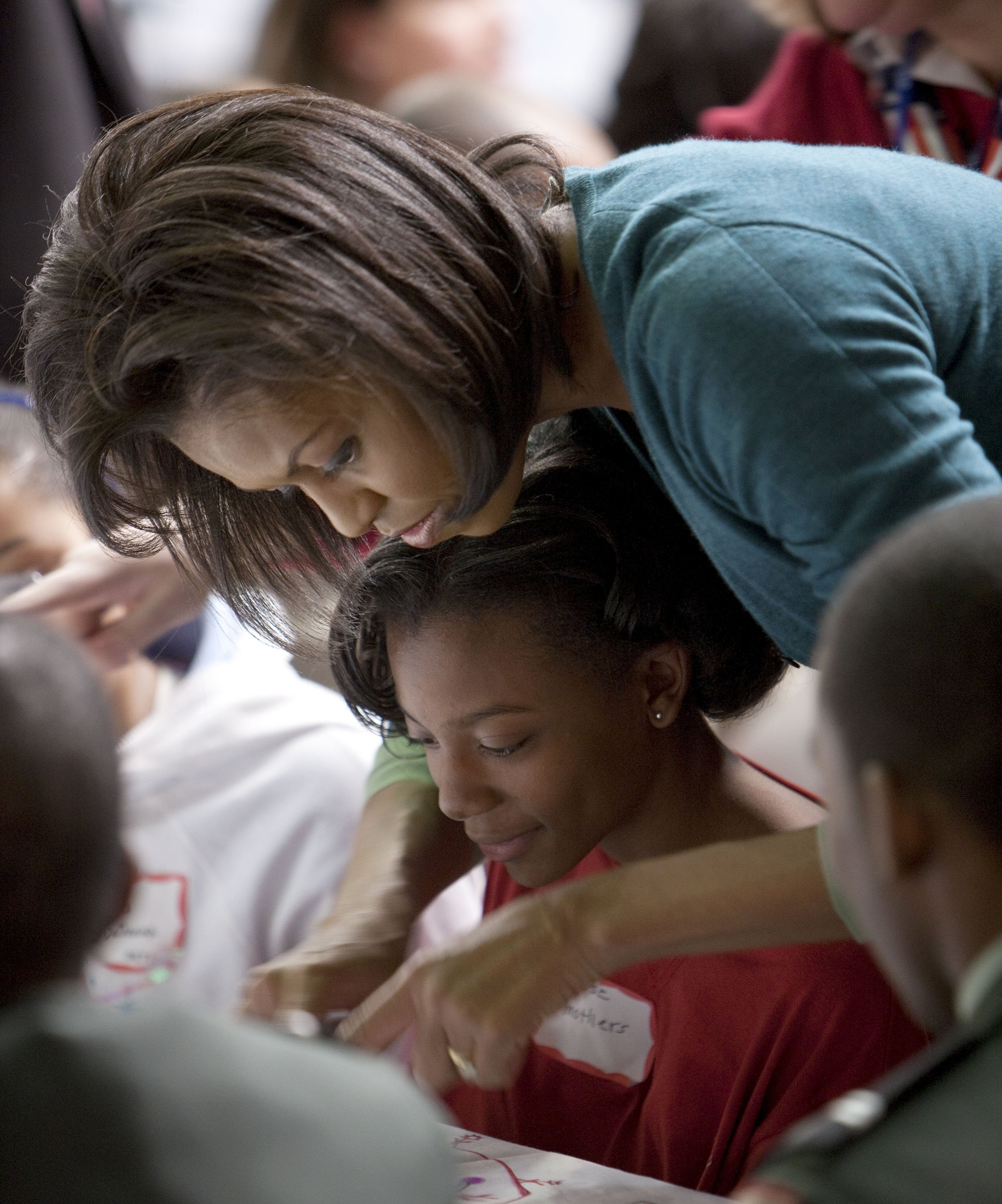 Michelle Obama helps a girl at Calvin Coolidge High School where students, military families, and volunteer service groups are working on various projects supporting the troops on January 19, 2009, in Washington, DC. | Source: Getty Images.