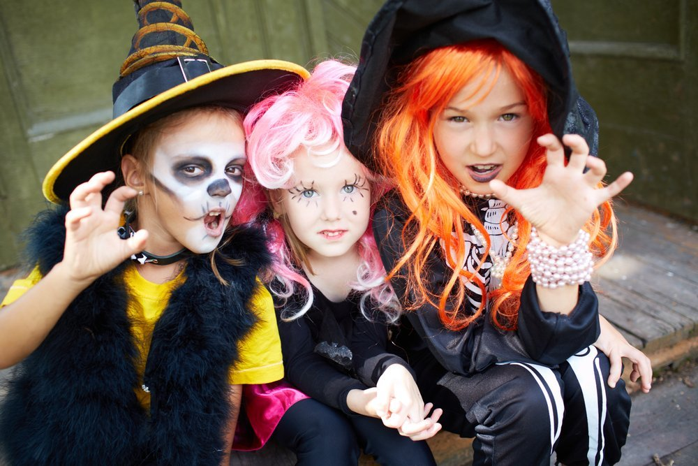 Three girls in Halloween costumes make gesture | Photo: Shutterstock