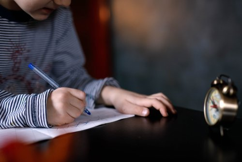 A boy writing a note. | Source: Shutterstock.