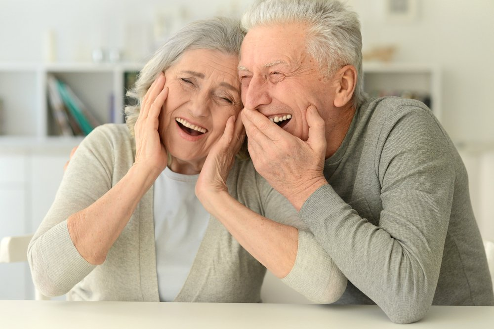 A close-up portrait of a happy senior couple posing at a home | Photo: Shutterstock/Ruslan Huzau