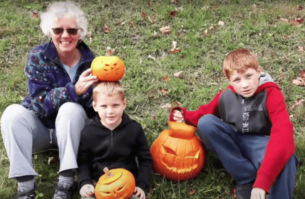 Grandmother who was kicked off a plane sits on the grass with her two grandchildren   Photo: Youtube/Inside Edition