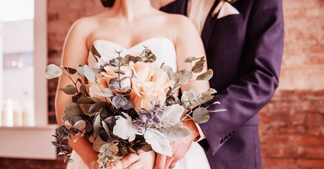 Husband and wife holding a bouquet on their wedding day | Photo:  unsplash.com/ohhbee