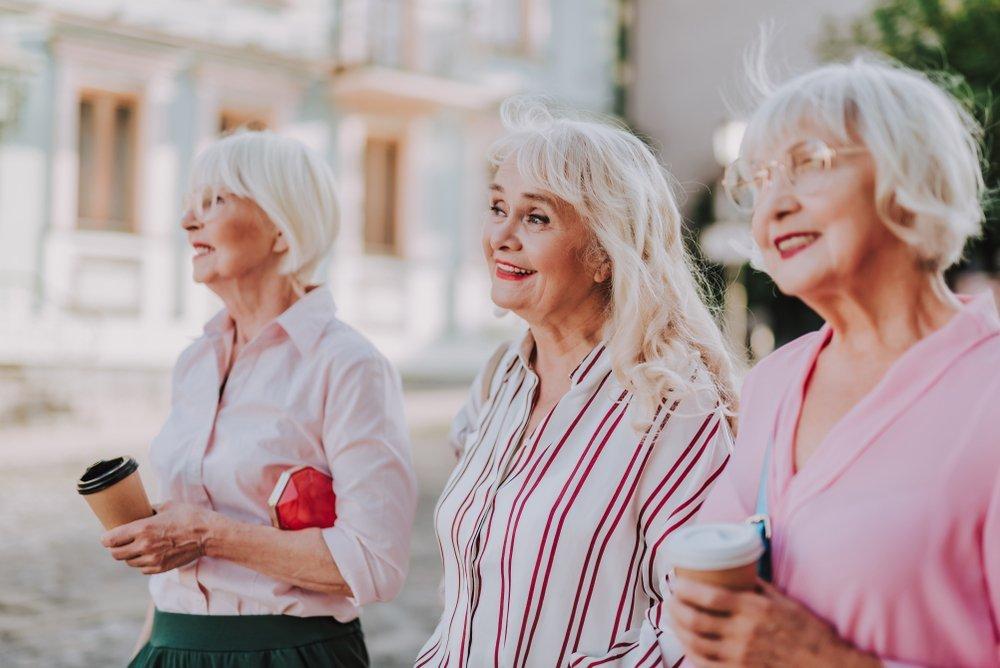 Tres abuelas con estilo caminando en la calle y sonriendo. Fuente: Shutterstock
