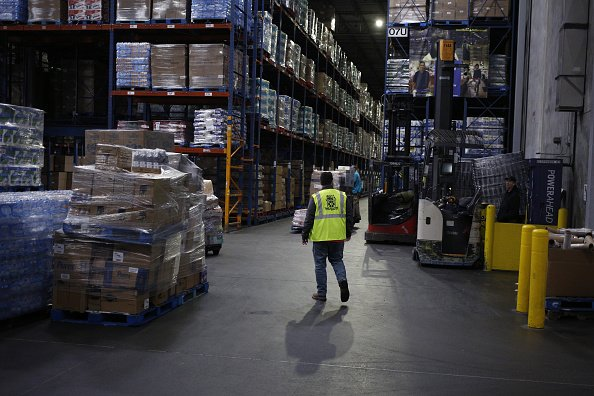 A worker walks past pallets of boxes at a Kroger Co. grocery distribution center in Louisville, Kentucky, U.S., on Friday, March 20, 2020. | Photo: Getty Images