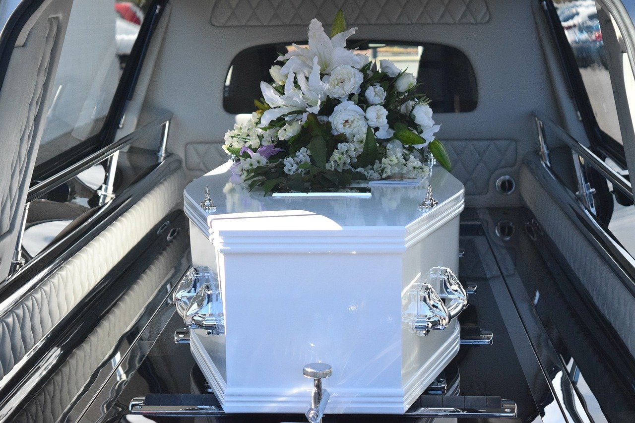 A coffin with flowers on top, placed inside the back of a hearse   Photo: Pixabay/Carolyn Booth