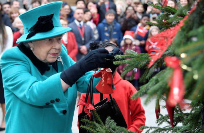 Queen Elizabeth attaches an ornament to a Christmas tree during the opening of the Queen Elizabeth II centre at CORAM, on December 05, 2018 in London, England | Source: Toby Melville - WPA Pool/Getty Images