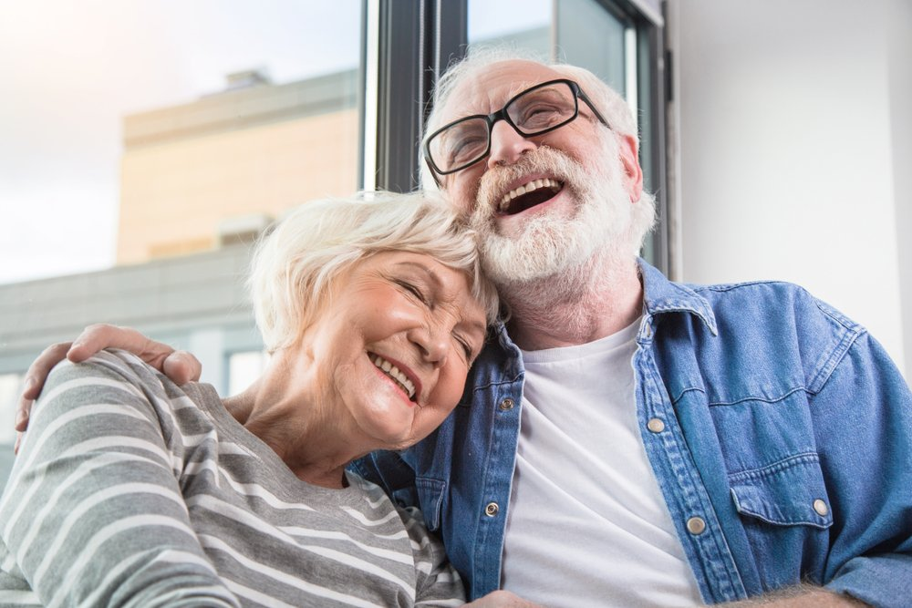 A waist up portrait of an old happy man and woman sharing a joke together | Photo: Shutterstock/Olena Yakobchuk