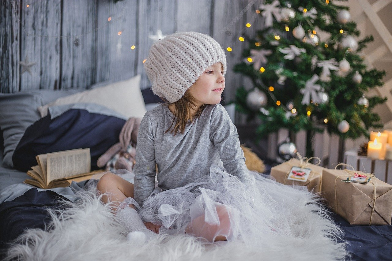 A little girl sitting on a bed and surrounded by Christmas presents, with a Christmas tree in the background. | Image: Pixabay.