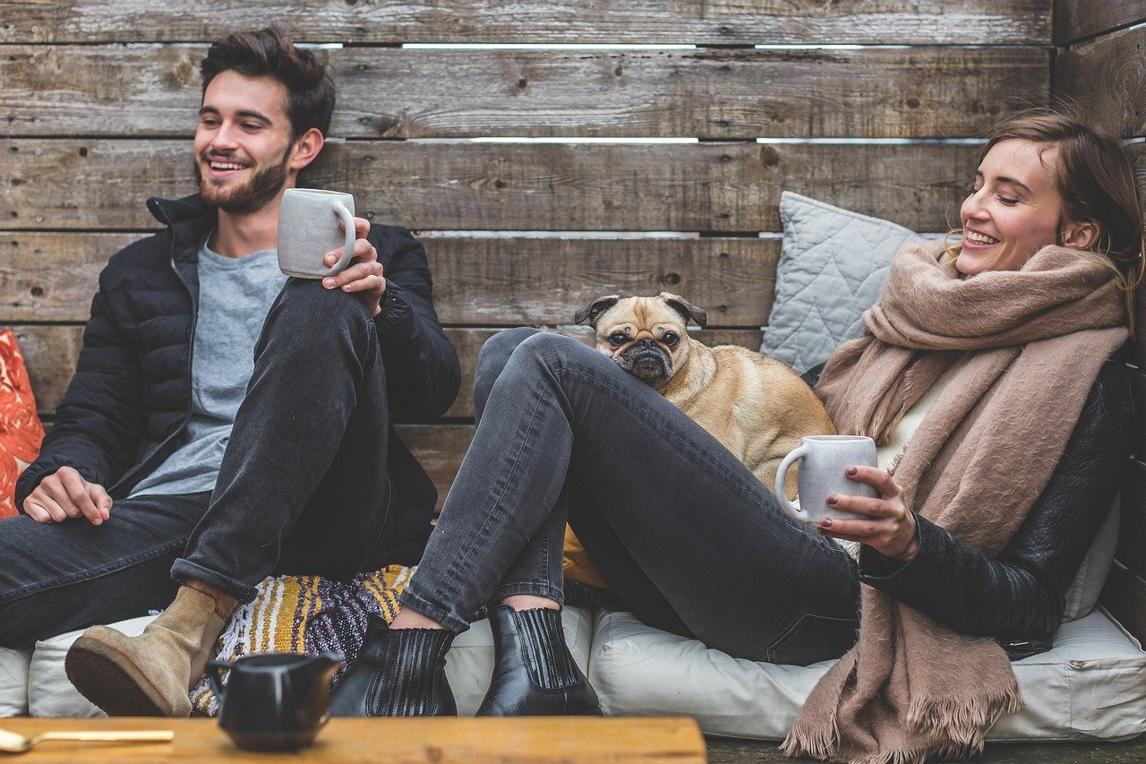 A man and woman laughing while sitting together with their dog   Photo: Pixabay/5688709