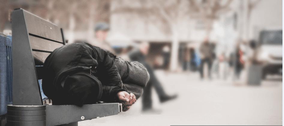 Un sans abris qui dort sur une banquette | Source : Shutterstock