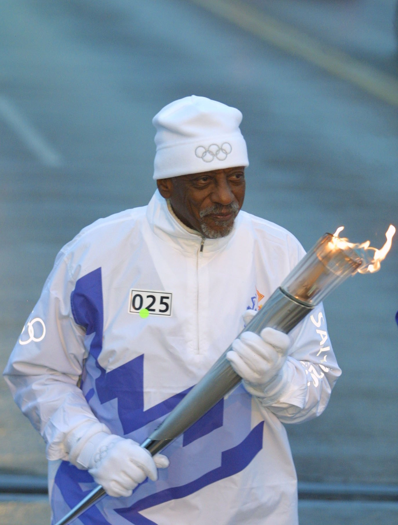 Harrison Dillard, an Olympic hurdler in the 1948 and 1952 Olympics, carries the Olympic Flame during the 2002 Salt Lake Olympic Torch Relay in Cleveland, Ohio | Photo: Getty Images