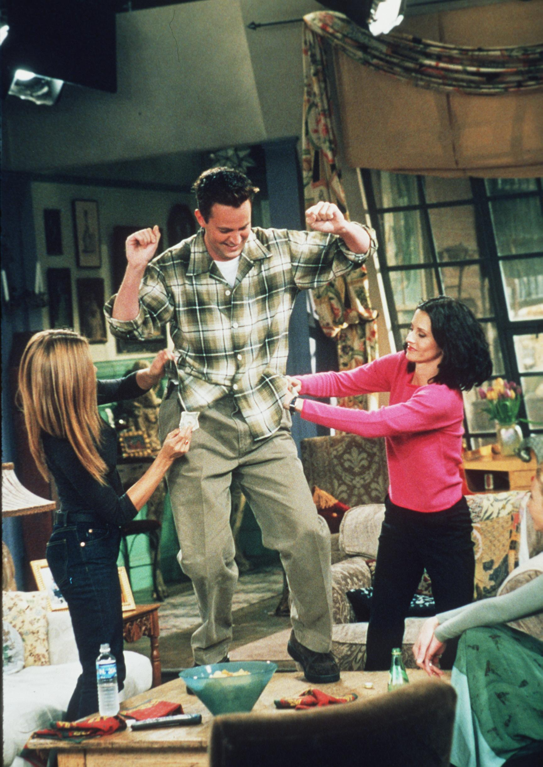 "Matthew Perry, Jennifer Aniston, and Courteney Cox in a 1999 episode of ""Friends."" 