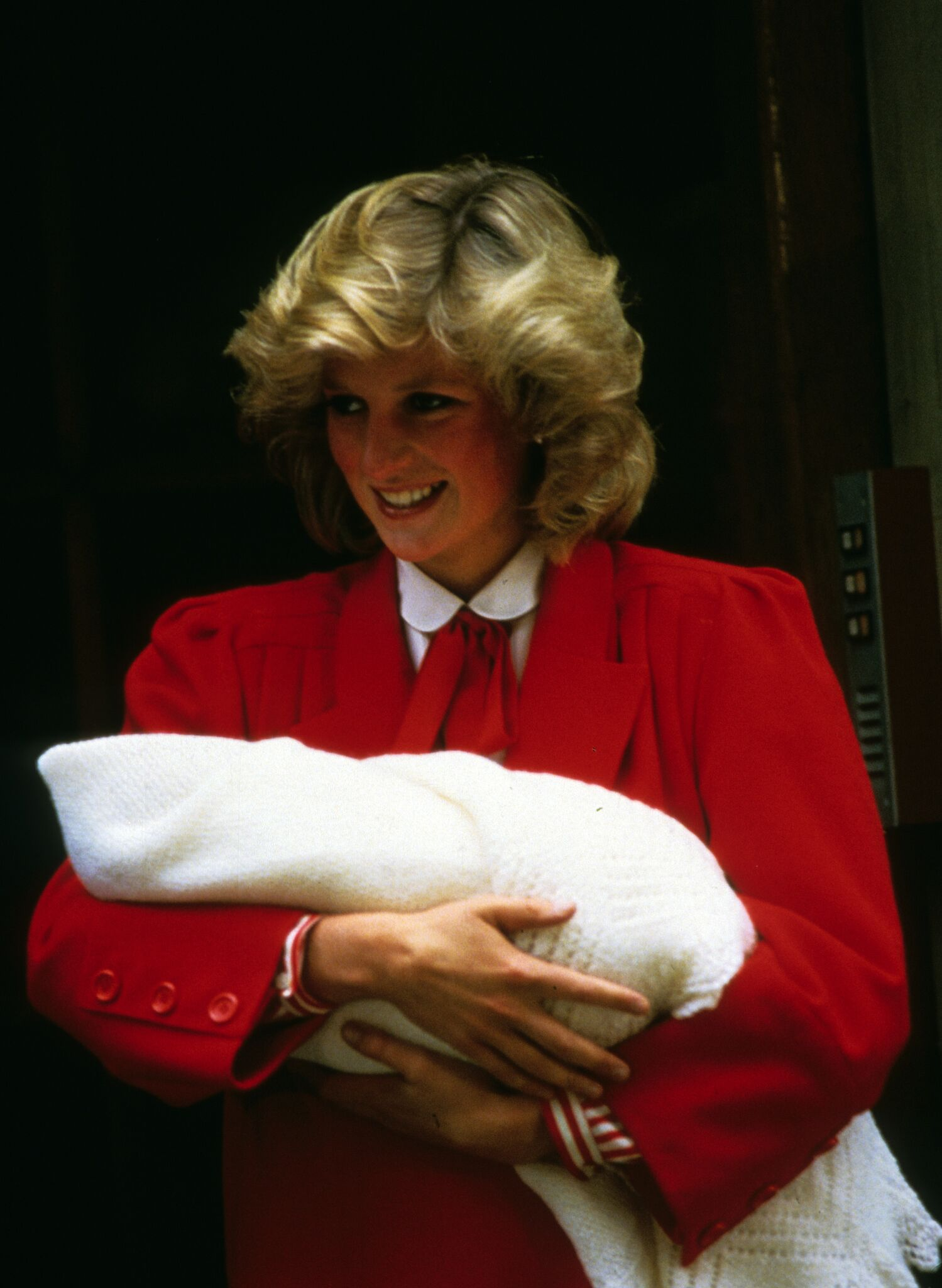 Princess Diana, Princess of Wales, smiles as she carries her newborn baby, Prince Harry when she leaves St. Mary's Hospital