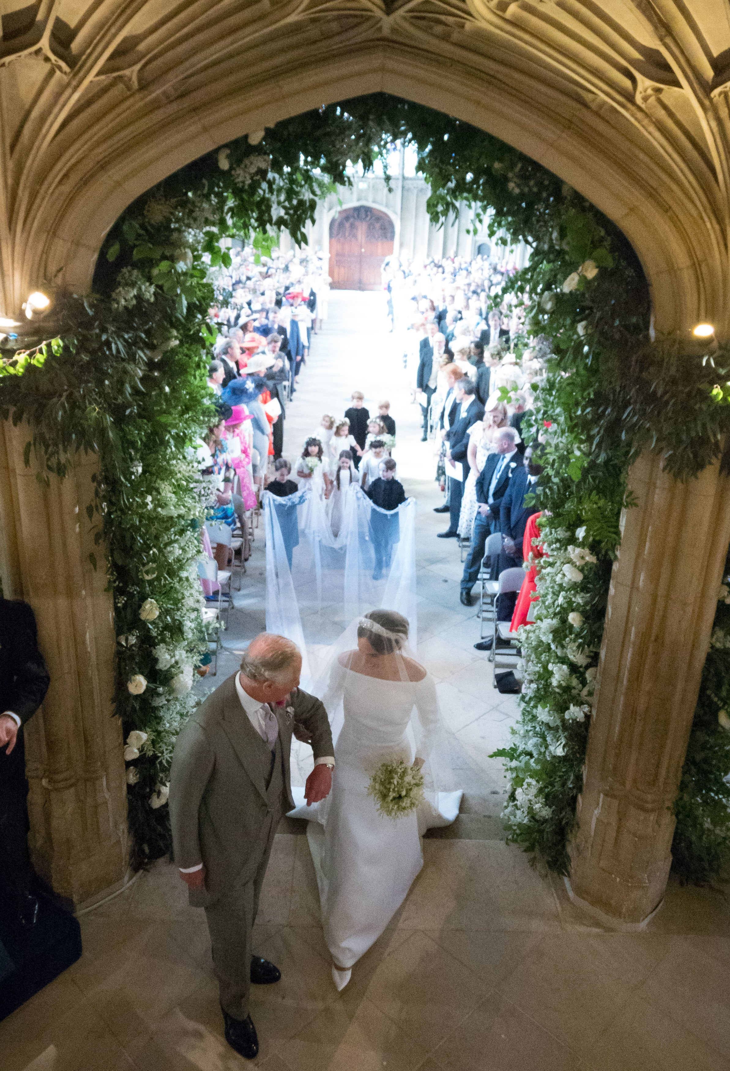 Meghan Markle, accompanied by Britain's Prince Charles, Prince of Wales walks down the aisle in St George's Chapel, Windsor Castle, in Windsor, on May 19, 2018 during their wedding ceremony. | Source: Getty Images