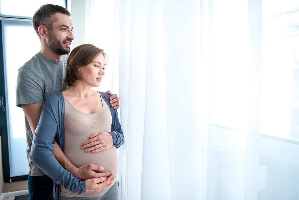 Soon-to-be parents looking over the window with joy and affection. | Photo: Shutterstock.