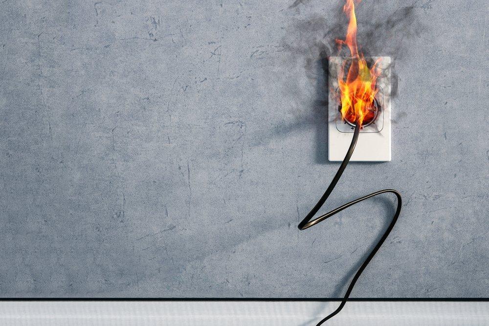 Incendio y humo en el enchufe del cable eléctrico por cortocircuito interior. Fuente: Shutterstock