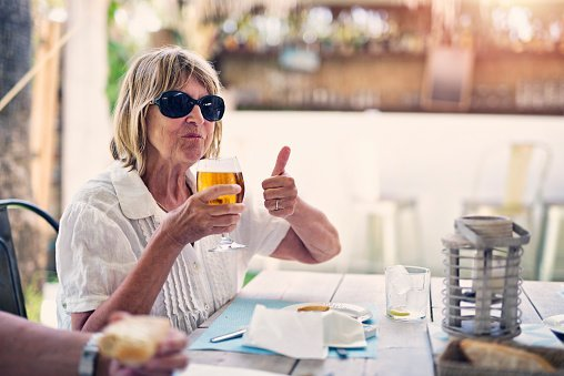 Photo of an old woman enjoying glass of cold beer in restaurant. | Photo: Getty Images