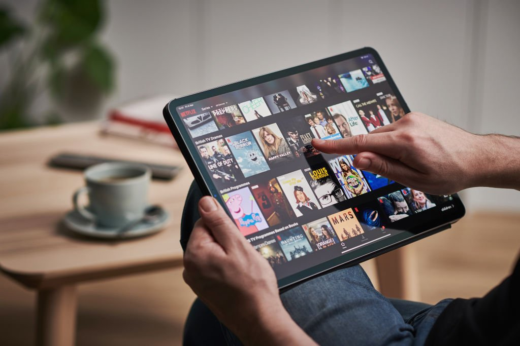 A photo of a man scrolling through Netflix on an Apple iPad Pro. | Photo: Getty Images.