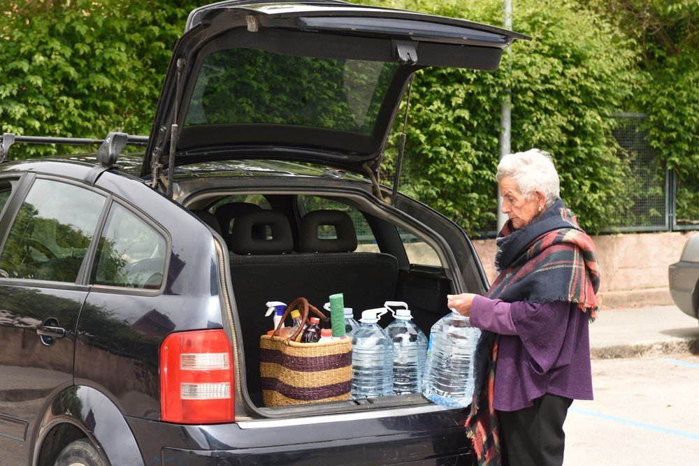 An elderly woman loading her car at a parking lot | Photo: Shutterstock