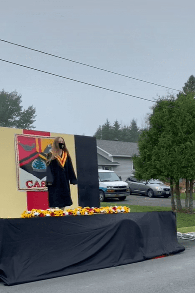 Canadian student standing on the Central Algoma SecondarySchool's (CASS) portable graduation stage while holding their high school diploma. │ Source: TikTok/leashorlando