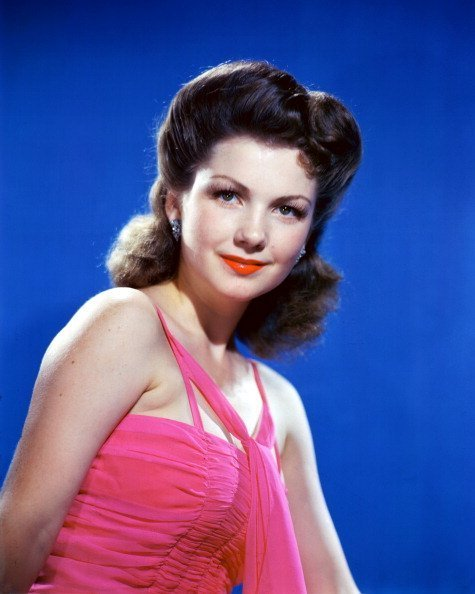 Anne Baxter (1923-1985), US actress, wearing a pink halterneck top in a studio portrait, against a blue background, circa 1945 | Photo: Getty Images