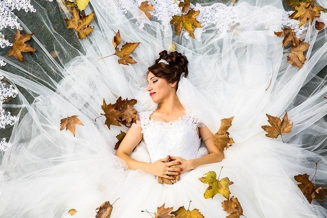 Woman in wedding dress lies on grass with train spread out beneath her | Photo: Pixabay