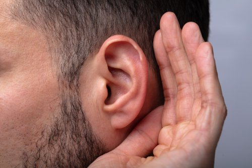 A close up of a man trying to hear. | Source: Shutterstock.