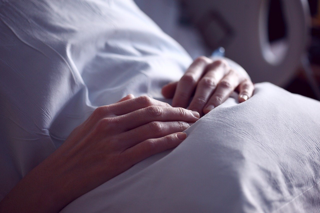 A person clutching at their stomach while laying in a hospital bed   Photo: Pixabay/Sharon McCutcheon