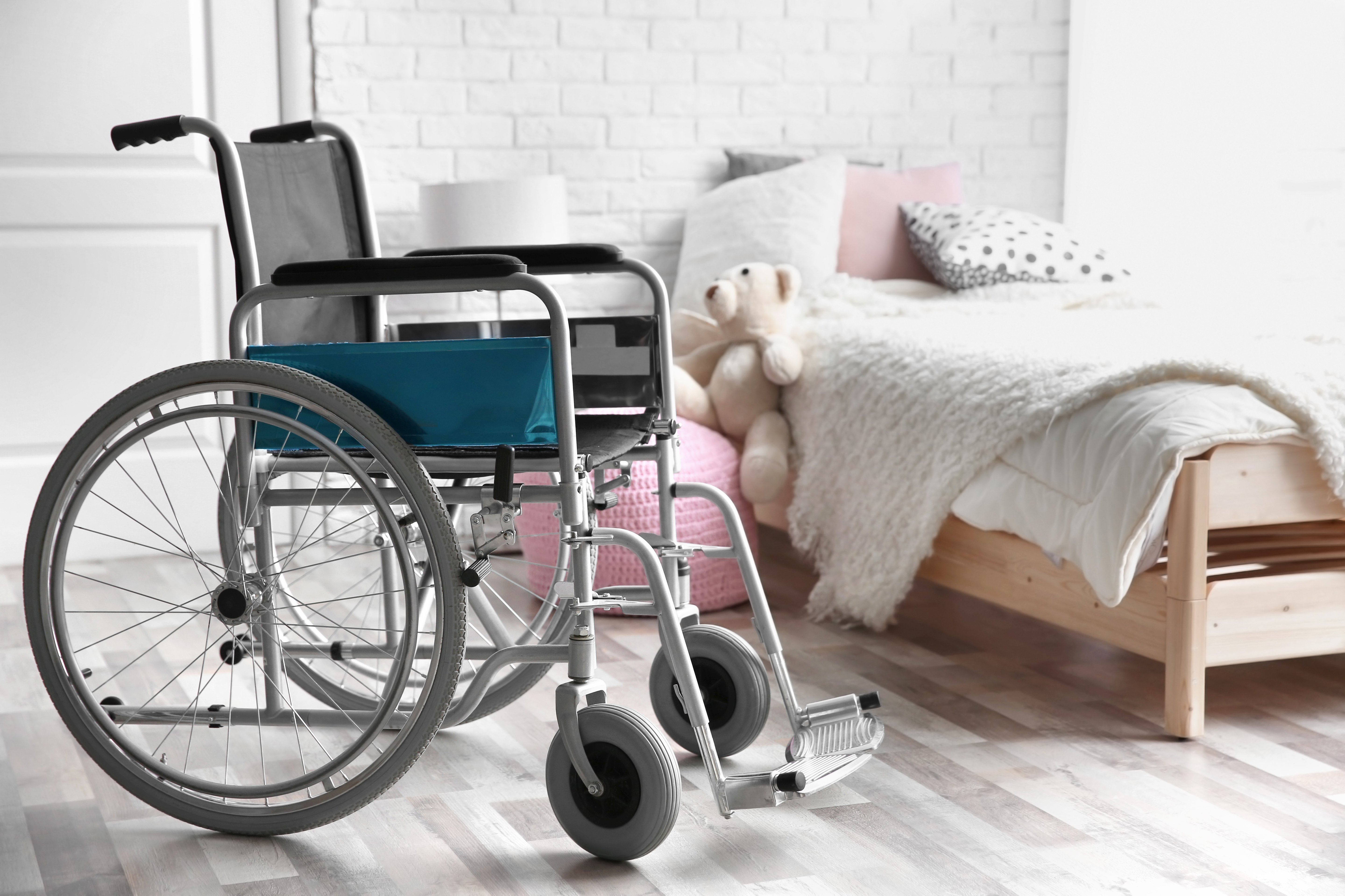 Picture of empty wheelchair next to a bed. | Source: Shutterstock